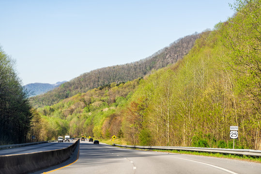 Smoky Mountains near Asheville, North Carolina at Tennessee border during sunny spring day sky green trees South 25 highway road with cars driving