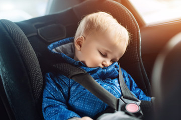 Cute caucasian toddler boy sleeping in child safety seat in car during road trip. Adorable baby dreaming asleep in comfortable chair during journey in vehicle. Children care and safety on roads