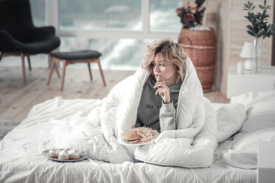 Woman eating junk food in her bed after breakup with boyfriend