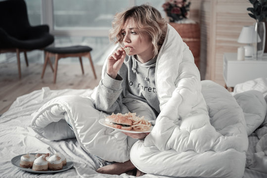 Sad and lonely woman eating burger and French fries in the bed