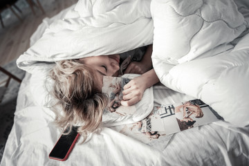 Young woman lying under blanket with photos with ex boyfriend