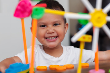 A hispanic boy with big smile while he plays with colorful building toys and learns to count with elementary manipulative toys.