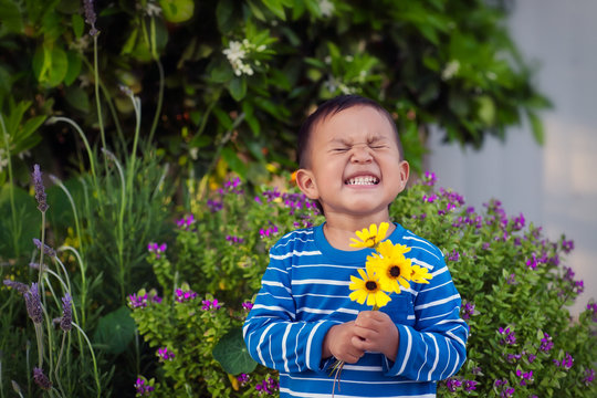 A cheerful young boy holding a few hand picked yellow flowers during spring time, standing in front of a lush garden.