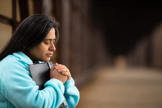 Hispanic Woman Sitting On A Bridge Praying While Holding Bible