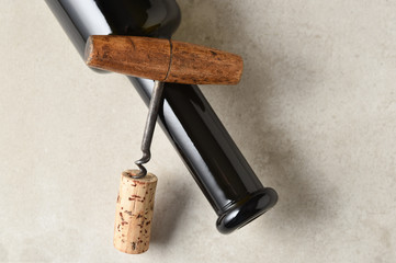 Wine bottle laying on its side with a corkscrew and cork