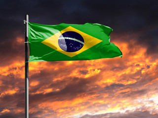 Foto op Canvas Brazilië flag of Brazil on flagpole fluttering in the wind against a colorful sunset sky