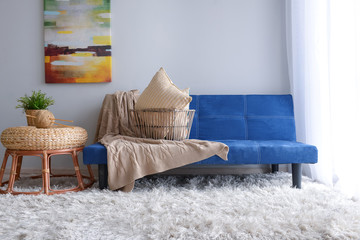 Stylish blue sofa in interior of living room