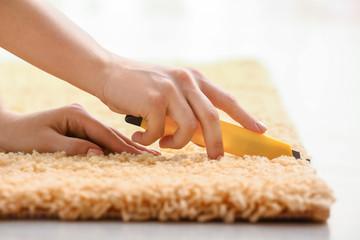 Woman cutting carpet at home, closeup
