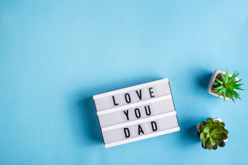 Love you dad is written on a decorative lamp on a blue background next to the succulents. Father's Day Background Concept. Top view, flat lay