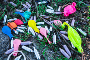 metal bulb and balloons for  laughing gas, party drugs, on grass field