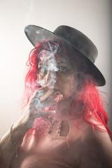 Hübsche Frau mit Hut, Zigarre und roten Haaren