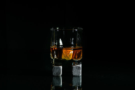 glasses made from whiskey on a glass table are isolated on a black background, special stones for whiskey. glass objects