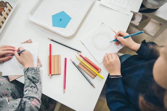 Montessori Education. Montessori School. Learning materials in a montessori methodology school. Geometric materials. Color pencils. Little girls drawing on paper.