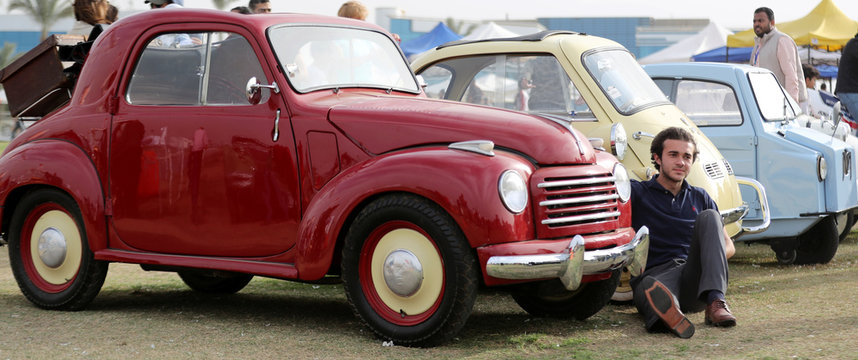A man sets beside a red classic Fiat 500C Topolino during the 7th Cairo Classic Meet in Cairo