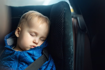 Cute caucasian toddler boy sleeping in child safety seat in car during road trip. Adorable baby dreaming asleep in comfortable chair during journey in vehicle. Children care and safety on roads Wall mural