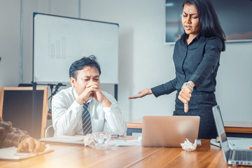 Serious woman boss scolding marketing team employee for bad business result with thumb down in meeting