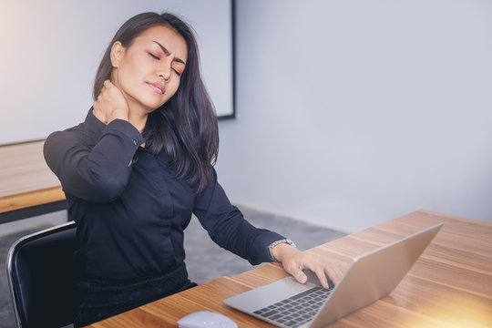 Working woman face suffering because of neck painful from working with computer laptop