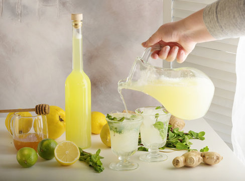 Bottle of homemade juice with ginger and lemon on light background. Horizontal