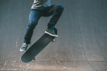 Skateboarder in action. Extreme sports lifestyle. Hipster performing ollie trick. Cropped shot. Copy space.