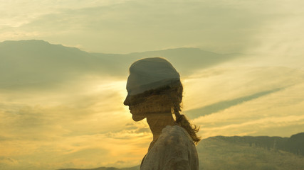 warm profile double exposure portrait of young woman with plaited hair during dusk