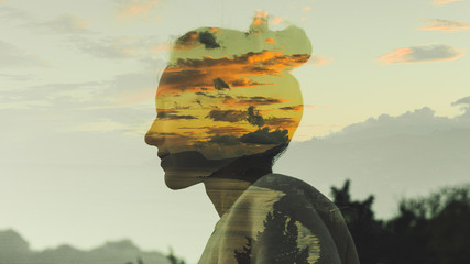 warm profile double exposure portrait of young woman with hair bun during dusk