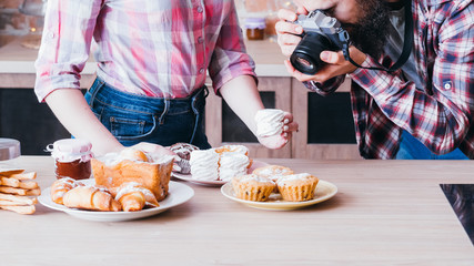 Food photographer and assistant at work. Man and woman taking photo of meringue. Cakes and pastries assortment around.