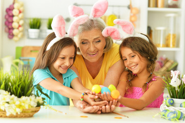 Portrait of happy grandmother and granddaughters coloring Easter eggs