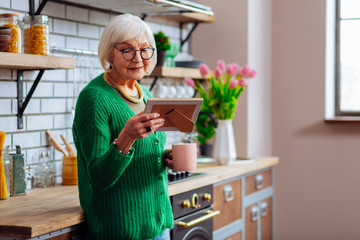 Aged woman looking at picture frame and enjoying morning coffee