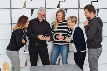Group of colleagues laughing looking at smartphone