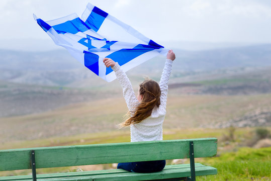 Beautiful young jewish girl sitting holding Israel flag in the wind and enjoying great view landscape on the sky, field and mountains.Patriotic holiday. Independence day Israel - Yom Ha'atzmaut .