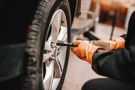 Close up of auto mechanic using wrench and changing tire in workshop.