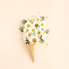 Wall Mural - Waffle cone with chamomile flower, leaves on beige background. Flat lay, top view floral background.