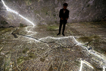 """A museum staff member walks with mobile devices over a giant illuminated aerial photograph of Berlin at the exhibition """"The Stasi in Berlin"""" inside former Stasi prison in Berlin"""