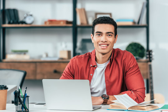 Smiling student in red shirt sitting at table and using laptop