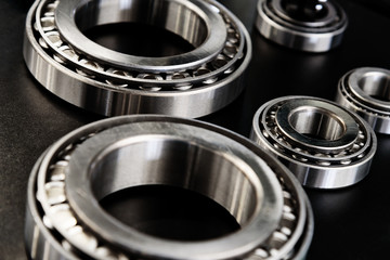 Full frame industrial background - metal bearings in close-up on a black background.