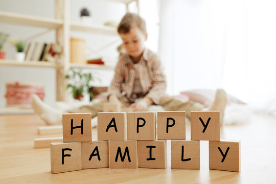 Wooden cubes with words HAPPY FAMILY in hands of smiling little boy at home. Conceptual image about child rights, education, childhood and social problems.