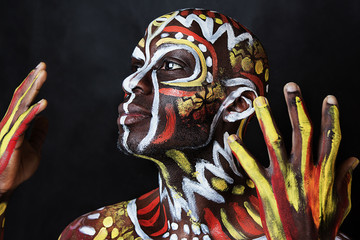 Close up portrait of strong emotional African-American guy. Ethnic African painting. Nigerian Body Art. Professional colorful makeup
