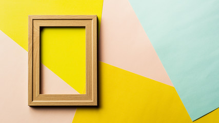 empty classic wooden photo frame on pink, yellow and blue background.