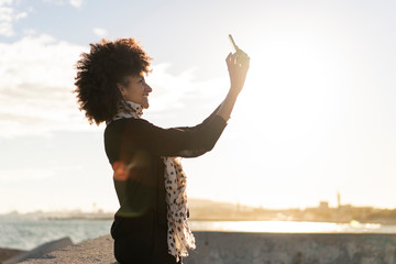 Smiling woman taking selfie with smartphone near the sea