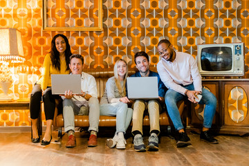 Group of smiling people sitting on couch in vintage living room with laptops