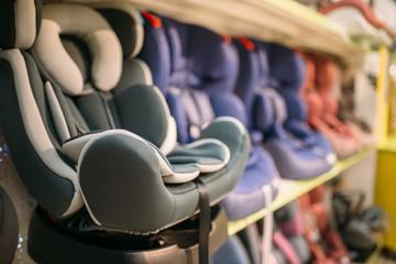 Child car seats variety on shelf in store, nobody