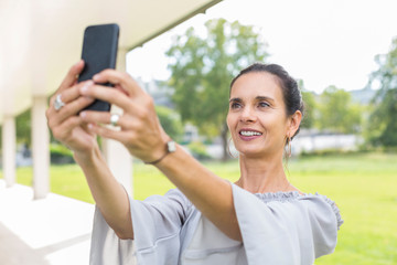 Portrait of smiling mature woman taking selfie with smartphone outdoors