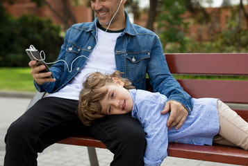 Portrait of smiling boy with father using cell phone and earbuds on a bench