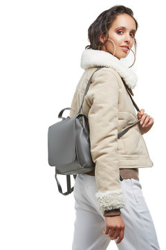 Three quarter half-turn shot of young lady, wearing short shearling coat and white trousers. The woman with hoop earrings is holding a shoulder strap of a backpack on her shoulder, looking at camera.