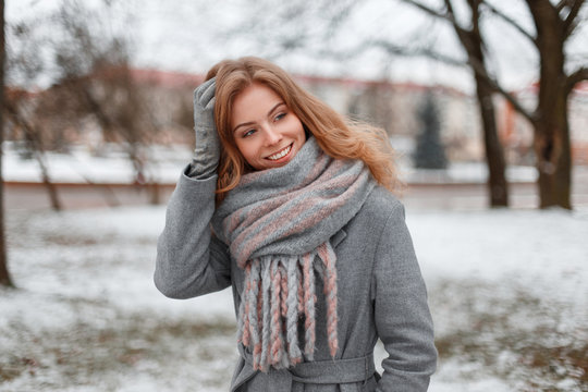 Cute attractive pretty young woman in gray gloves in a trendy gray coat with a vintage knitted scarf is standing and smiling in a snowy park. Positive happy girl travels in winter day.