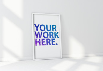 White Vertical Poster Frame Leaning on Wall Mockup