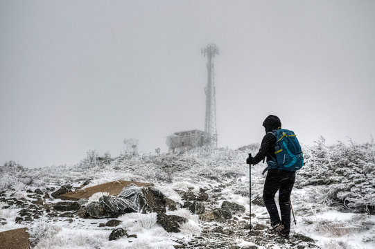 Woman hiking mount Sugarloaf during winter snow storm, Maine, USA