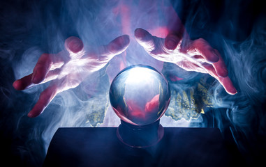 a fortune teller holds her hands over a crystal ball