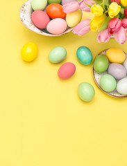 Easter eggs decoration spring tulip flowers yellow background