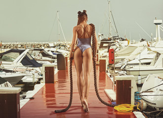 Woman with a slim figure is standing on a wooden pier in a yacht club